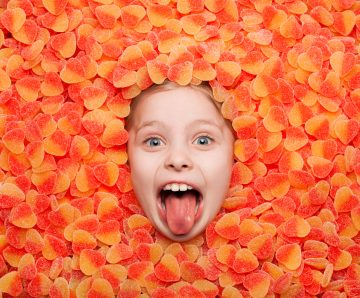 Little child lying in fruit jelly showing out tongue and looking at camera.